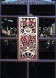 Röd och guld krävd panel i fönster Royaltyfri Bild