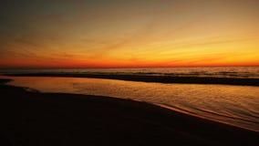 Röd och orange himmel över havet på solnedgången Arkivfoto