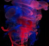 Röd och purpurfärgad färgpulverakryl som tappar i vatten Royaltyfria Bilder