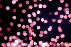 Röd och rosa julgranbokeh på svart bakgrund av defocused blänka ljus, begrepp för julbakgrundsmodell royaltyfria bilder