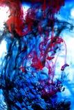 Röd och svart färgpulver för blått, i vatten Royaltyfria Bilder