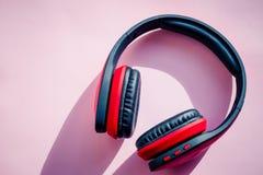 Röd och svart hörlurar på rosa bakgrund lyssnar musik Minimalismidébegrepp royaltyfri fotografi