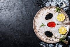 Röd och svart kaviar i skedar Arkivfoton