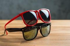 Röd och svart solglasögon på en tabell Arkivfoto