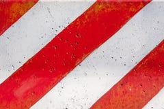 Röd och vit gjord randig barriärtextur för konkret väg Arkivfoton