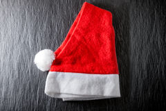 Röd och vit hatt för jultomten` s på svart bakgrund Royaltyfria Foton
