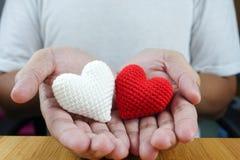 Röd och vit hjärta i manhänder Arkivbilder