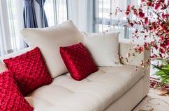 Röd och vit kudde på den moderna vita soffan arkivbild