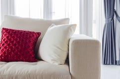 Röd och vit kudde på den vita soffan Arkivbild