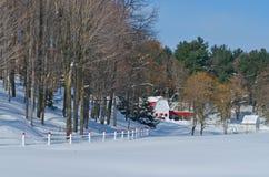 Röd och vit ladugård med att matcha staketet Arkivfoto
