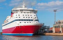 Röd och vit passagerarfärja som förtöjas i port Arkivfoto