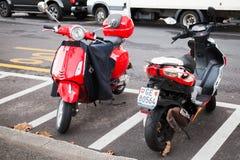 Röd och vit sparkcykelställning på parkering Arkivfoto