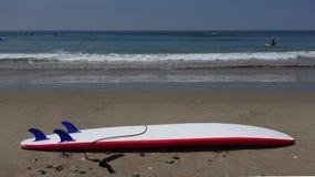 Röd och vit surfingbräda på stranden Royaltyfri Bild