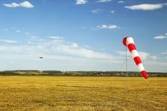 Röd och vit windsockvindsocka på blå himmel, gult fält och molnbakgrund arkivfoton