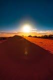 Den röda sanddynen med skvalpar och slösar skyen Arkivfoto