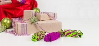 Röd påse med gåvor och julleksaker för julgranen, på vit arkivfoto