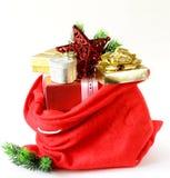 Röd påse mycket av julgåvor Arkivfoton