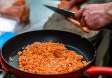 Röd panna med högen av Cutted Salmon Pieces i förgrunden, Mal royaltyfri fotografi
