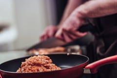 Röd panna med högen av snittet Salmon Pieces i förgrunden, manlig kock Cutting Fresh Salmon på träbrädet i bakgrunden - royaltyfri fotografi