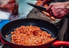 Röd panna med högen av snittet Salmon Pieces i förgrunden, manlig kock Cutting Fresh Salmon på träbrädet i bakgrunden - royaltyfri bild