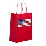 Röd pappers- bärkasse, shoppare, med USA-flaggan arkivfoton