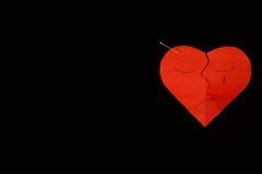 Röd pappers- bruten hjärta på svart bakgrund med stiftet Arkivbild