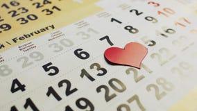 Röd pappers- hjärta visas på kalendern på 14th Februari Valentin dag - ferien av förälskelse arkivfilmer