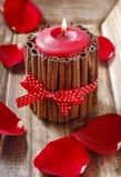 Röd parfymerad stearinljus som dekoreras med kanelbruna pinnar Royaltyfri Bild