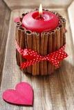 Röd parfymerad stearinljus som dekoreras med kanelbruna pinnar Royaltyfri Fotografi