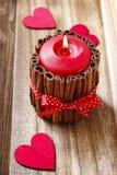 Röd parfymerad stearinljus som dekoreras med kanelbruna pinnar Fotografering för Bildbyråer