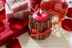 Röd parfymerad stearinljus som dekoreras med kanelbruna pinnar Rosa kronblad a Arkivfoto