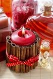 Röd parfymerad stearinljus som dekoreras med kanelbruna pinnar Rosa kronblad a Arkivbilder