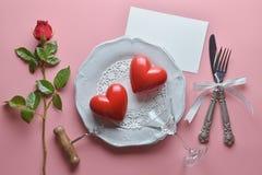 Röd parhjärta, vinöppnare, coctailexponeringsglas på den vita maträtten, med gaffeln och kniven i band, ros, på rosa bakgrund royaltyfria bilder