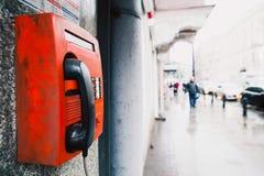 Röd payphone på väggen Royaltyfria Bilder