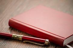 Röd penna och notepad Royaltyfri Bild
