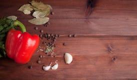 Röd peppar, örter och kryddor på mörkt trä Arkivbild