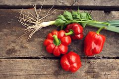 Röd peppar och salladslökar på ett trä bordlägger Royaltyfria Bilder