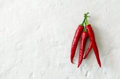 Röd peppar på den gamla kalkade yttersidan Arkivfoto