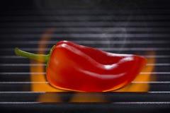 Röd peppar på ett varmt flammande grillfestgaller Royaltyfri Fotografi