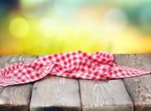 Röd picknicktorkduk på mogen bokehbakgrund för trätabell Arkivfoto