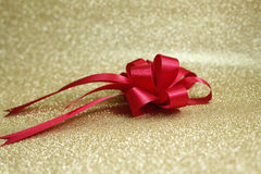 Röd pilbåge och bakgrund i guld Royaltyfri Foto
