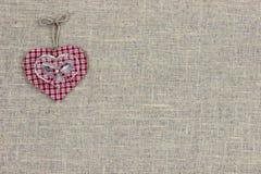 Röd plädlandshjärta som hänger på säckvävtecken Royaltyfria Foton