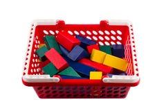 Röd plast- shoppingvagn med träkonstruktionskvarter på whi Arkivbild