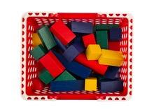 Röd plast- shoppingvagn med träkonstruktionskvarter på whi Arkivfoto