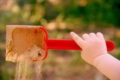 Röd plast- skopaskopa i en hand för barn` s Lek i sandlådan Med en skopa av sandnedgångar Symbol av barndom och gyckel royaltyfri foto
