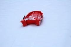 Röd plast- släde i snöig fält Arkivfoton