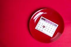 Röd platta med ett stycke av kalendern royaltyfria foton