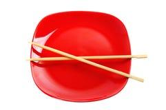 Röd platta med kinesiska sticks Fotografering för Bildbyråer