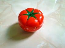 Röd pomodorotidmätare i tomatform på en svart texturbakgrund royaltyfria foton
