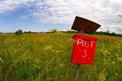 Röd poststolpeask i ett fält Arkivbild